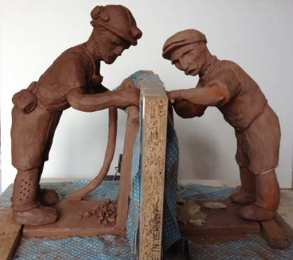 This shows both of the figures standing in their own separate mines. The modern miner is taller as the clay is still wet and he will shrink down to the same size as the other chap.